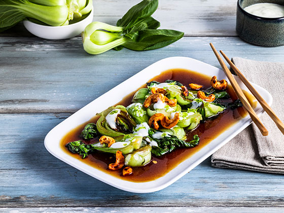 Fried pak choi with teriyaki sauce, chili cashew nuts and lime yoghurt dip